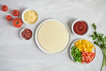 Fresh dough pizza base and ingredients on a white table. Top view.