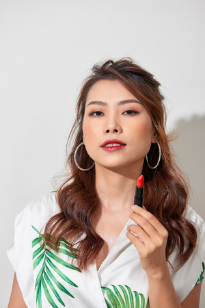 Close up beauty portrait of young woman with clean fresh perfect skin and nude makeup look at camera and holding lipstick