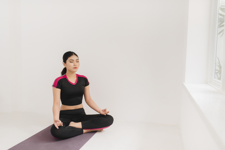 A woman practices yoga near the window