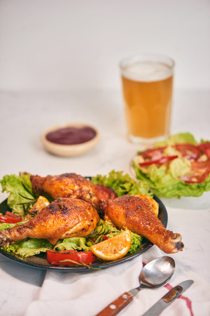 Grilled chicken legs roasted on the grill on dark plate with tomato sauce in a bowl and lettuce leaves, glass mug of beer Stok Fotoğraf