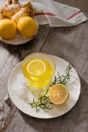 Ginger tea with lemon, ginger root and rosemary on wooden background. Small glass transparent pitcher with hot drink. Seasonal beverages. Shallow DOF, selective focus, focus on top of pitcher.