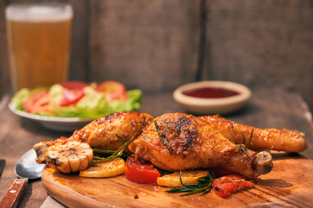 Chicken drumtick in on wood board Stock Photo
