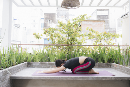 Asian woman relax in the holiday. Play if yoga. On the balcony 写真素材