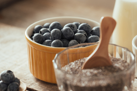 Fresh blueberries, almond and chia seeds with milk on wooden board. Ideal healthy breakfast concept.