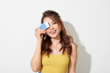 Portrait of an excited happy asian woman holding credit card isolated over white background 版權商用圖片