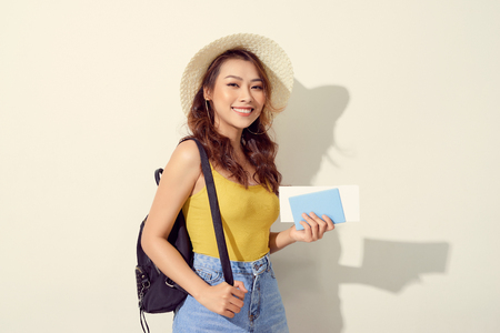 Portrait of young woman wearing trendy outfit, straw hat, travel with backpack  and holding flight ticket, passport 版權商用圖片