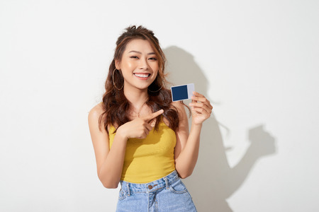 Foto der jungen lächelnden asiatischen Frau, die Karte hält