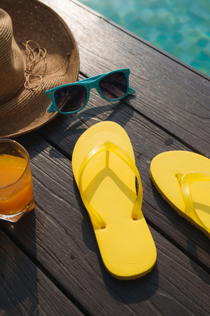 Hat, sunglasses and flip flops by swimming pool