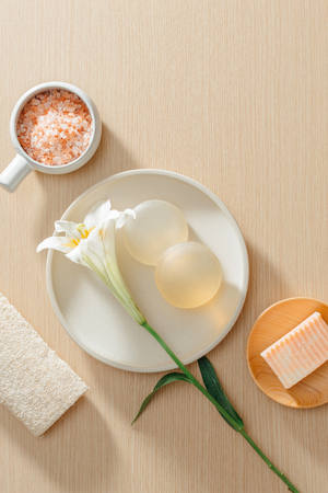 Top view of organic spa skincare products with salt, flowers, natural soap, towels and pumice stone Stock Photo