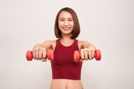 Woman is exercising with dumbbells