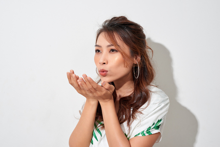 Beautiful young Asian woman blow a kiss isolated on white background. 版權商用圖片