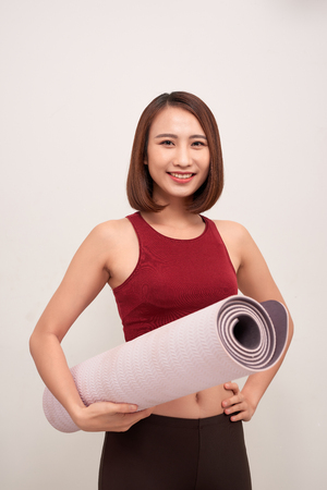 exercise fitness woman ready for workout standing holding yoga mat Stock Photo