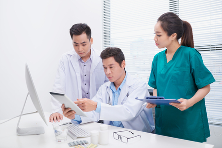 Group of doctors and nurses examining medical report of patient. Team of doctors working together on patients file at hospital. Reklamní fotografie