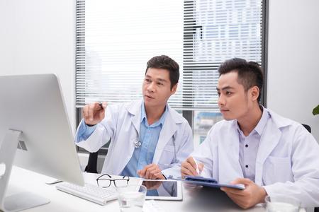 Médecins assidus examinant le dossier du patient Banque d'images