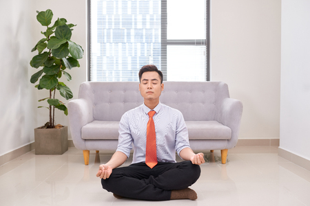 Businessman meditating in lotus pose on the floor in the office Stock Photo