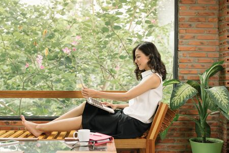Morning scene of young woman right hand writing on notebook beside window in cafe. Freelance working lifestyle