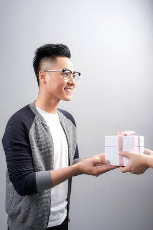 Jonge aziatische man die een geschenkdoos ontvangt van zijn collega op een witte achtergrond