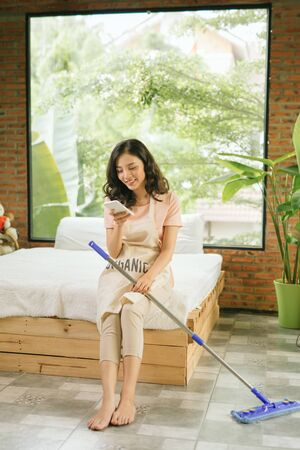 Beautiful young woman is holding a mop, using a smartphone and smiling while cleaning her house 免版税图像