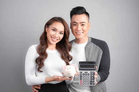 young couple hold pink pig bank and calculator isolated on gray background