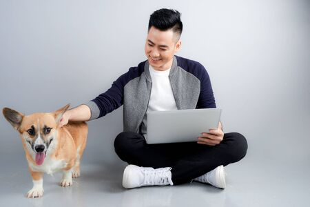 Handsome young businessman is using laptop while sitting with his dog on floor