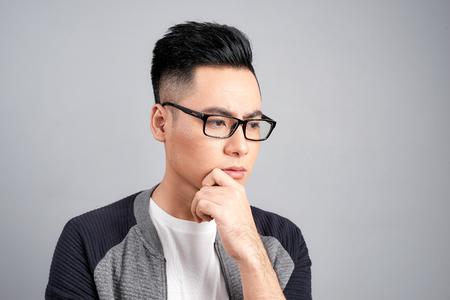 Studio shot of young Asian man thinking while wearing eyeglasses