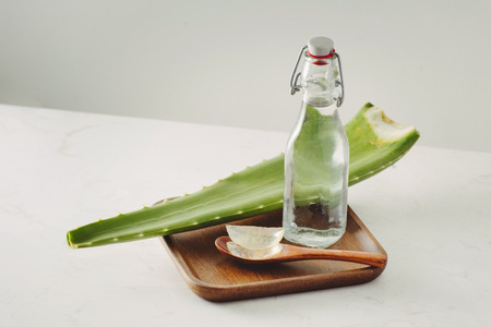 Aloe pieces, fresh leaves and bottle glass on a white background