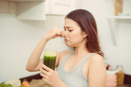 Woman drinking disgusting green smoothie, closing nose, bad smell and taste