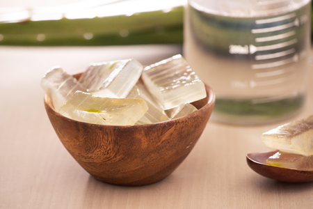 Bowl with peeled aloe vera and green leaves on wooden background 写真素材
