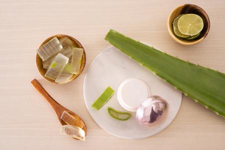 Jar of cream, peeled aloe, lemon and  aloe leave and chopped aloe on marble round board