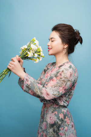 Interested young woman in cute dress in blue background 写真素材 - 123889466