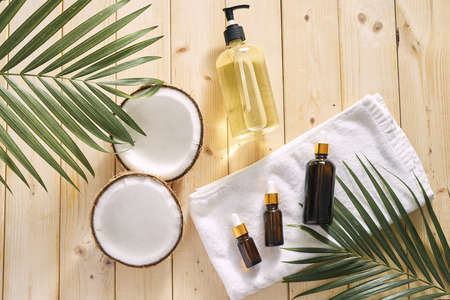 Cracked coconut and a bottle of oil on the table - spa, skincare, haircare and relaxation concept