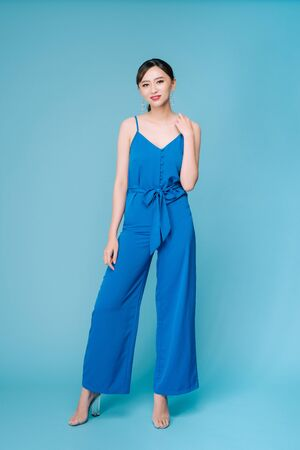 Young beautiful woman posing in new casual blue fashion costume dress with pants full body on blue background