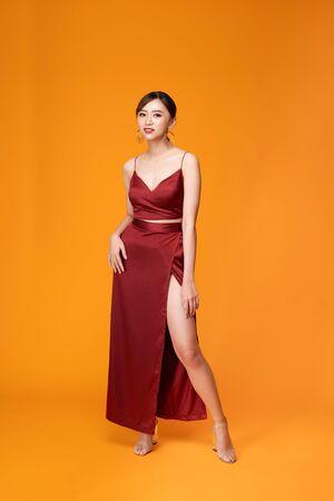 Ganzaufnahme der jungen Frau im roten Kleid, die vor gelbem Hintergrund steht und posiert