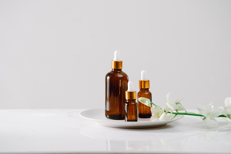 Spa setting with orchids and essential oil in a glass bottle, aromatherapy concept