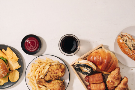 fast food and unhealthy eating concept - close up of fast food snacks and cola drink on white table Фото со стока