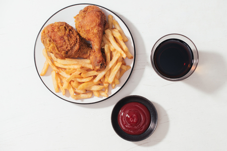 Fried breaded crispy chicken nuggets with French fries on wooden plate, ketchup and soft drink on the side 版權商用圖片