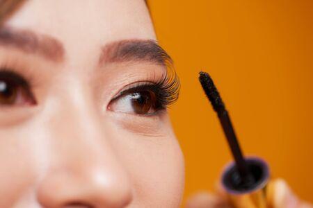 Beautiful woman applying mascara on her eyelashes Foto de archivo