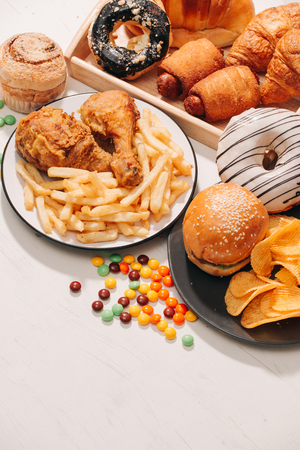 fast food and unhealthy eating concept - close up of fast food snacks and cola drink on white table 免版税图像
