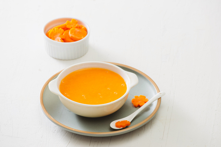 Carrot baby puree in bowl isolated on light background 스톡 콘텐츠