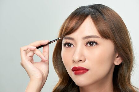 Asian young beautiful woman applying cosmetic powder brush on eyebrow, natural makeup, beauty face