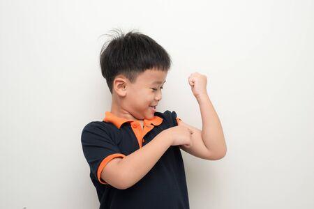 Jonge aziatische jongen die zijn biceps wijst om te vertellen dat hij sterk is Stockfoto