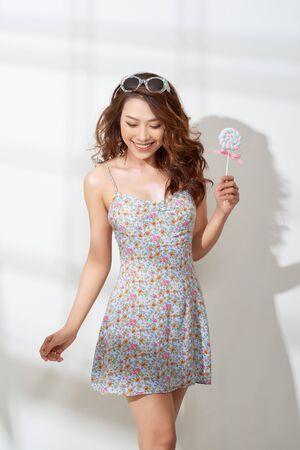 Atrakcyjna azjatycka kobieta w kwiecistej sukience z lizakiem w dłoni