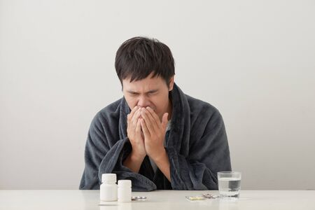 young sick and ill man in sofa holding tissue cleaning snotty nose having temperature feeling bad infected by winter grippe virus in flu and influenza health care concept.