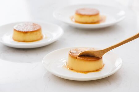 Delicious vanilla custard in caramel sauce with spoon