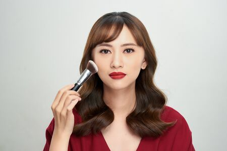 Beauty Asian Girl tan skin with Makeup Brushes. She smiling and looking to powder brush, Natural makeup
