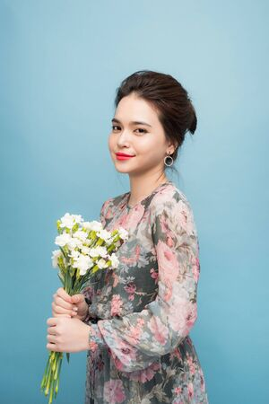 Interested young woman in cute dress in blue background 写真素材 - 124787779
