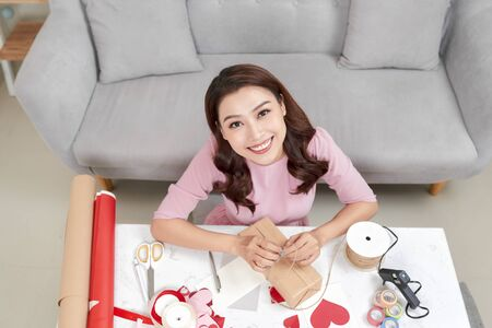 Woman wrapping Christmas gifts. Merry Christmas! Stock Photo