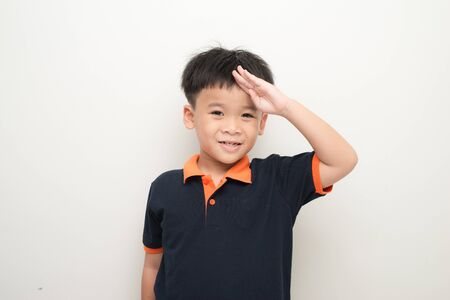 Cheerful little boy putting a hand on the forehead greeting, isolated on a white background.