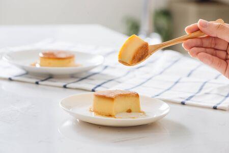 Pudín de flan de caramelo casero de corte de mano de mujer en plato blanco. Sobre mesa blanca con servilleta. Foto de archivo