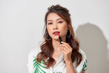 Beautiful young woman putting lipstick on lips Foto de archivo